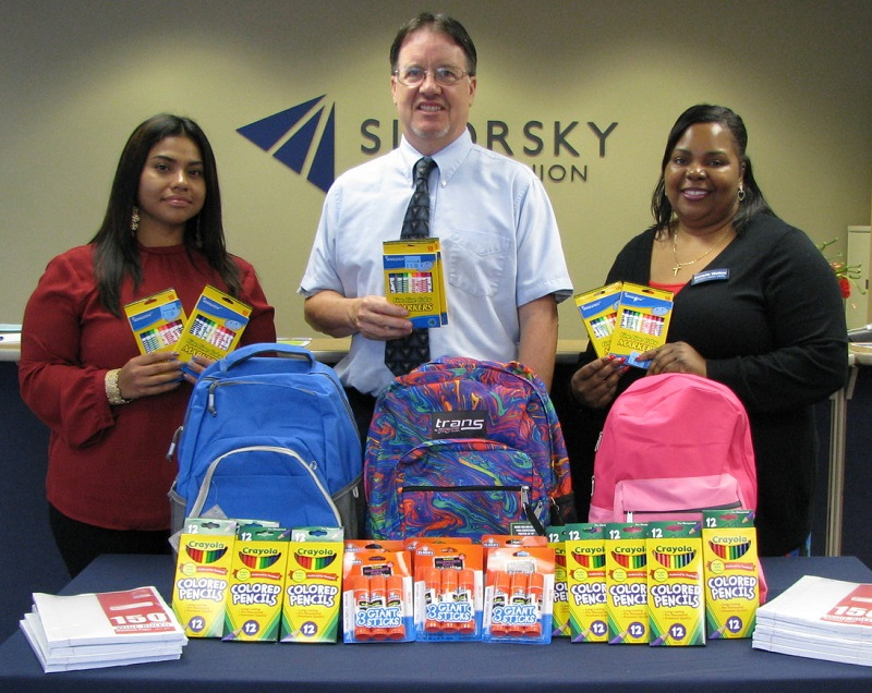 Sikorsky Credit Union Employees with backpacks and school supplies